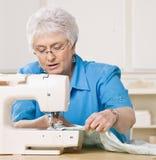 Vrouw die naaimachine thuis met behulp van Royalty-vrije Stock Afbeelding