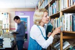 Vrouw die naar nieuw boek zoeken stock afbeelding