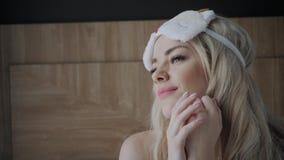 Vrouw die naar slaap voorbereidingen treffen te gaan en op een slaapmasker zetten Blinddoek op oog Ochtend in hotelruimte Wit hoo stock video