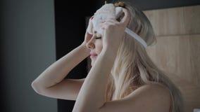 Vrouw die naar slaap voorbereidingen treffen te gaan en op een slaapmasker zetten Blinddoek op oog Ochtend in hotelruimte Wit hoo stock videobeelden