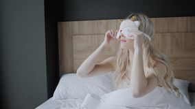 Vrouw die naar slaap voorbereidingen treffen te gaan en op een slaapmasker zetten Blinddoek op oog Ochtend in hotelruimte Wit hoo stock footage