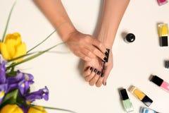 Vrouw die nagellak toepassen dichtbij flessen op witte lijst met bloemen royalty-vrije stock afbeelding