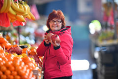 Vrouw die nar fruit kopen op marktplaats Royalty-vrije Stock Afbeeldingen