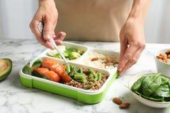 Vrouw die natuurlijk eiwitvoedsel zetten in container royalty-vrije stock foto