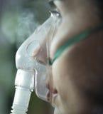 Vrouw die nebuliser masker gebruiken stock fotografie