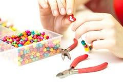Vrouw die necklase van kleurrijke plastic parels op lichte achtergrond maken Stock Foto's