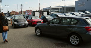 Vrouw die nieuw min, Mercedes-Benz, Audi-auto bij handelaar kopen stock videobeelden