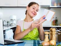 Vrouw die nieuw recept zoeken Stock Foto's