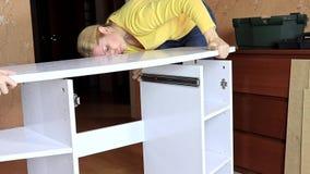 Vrouw die nieuw wit meubilair opzetten, zij die een tafelblad op een nieuwe half geassembleerde toilettafel zetten stock video