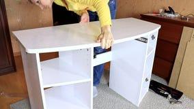 Vrouw die nieuw wit meubilair opzetten, zij die een tafelblad op een nieuwe half geassembleerde toilettafel zetten stock footage