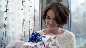 Vrouw die nieuwe jaargift overwegen De mooie jonge vrouw in sweater met glimlach en nieuwsgierigheid overweegt Kerstmisgift stock videobeelden