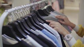 Vrouw die nieuwe kleren in een wandelgalerij kopen stock videobeelden