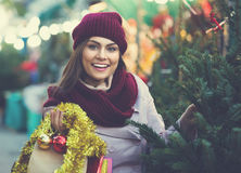 Vrouw die Nieuwe Year& x27 kiezen; s boom in markt Stock Afbeeldingen