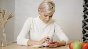 Vrouw die nota's maken en in handen cellulair houden stock videobeelden