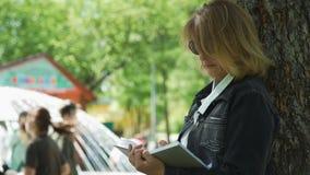 Vrouw die nota's nemen in notitieboekje bij een park stock footage
