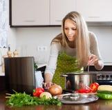 Vrouw die notitieboekje gebruiken terwijl het koken van soep Stock Foto's