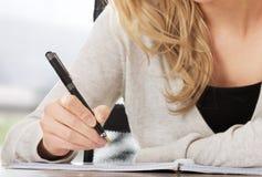 Vrouw die in Notitieboekje schrijven stock fotografie