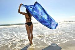 Vrouw die oceaan onder ogen ziet Stock Foto's