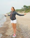 Vrouw die ochtendoefeningen op zee doen stock fotografie