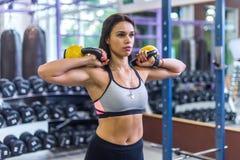 Vrouw die oefening met kettlebell doen bij gymnastiek Royalty-vrije Stock Foto