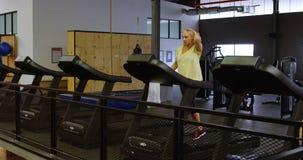 Vrouw die oefening op tredmolen in geschiktheidsstudio 4k doen stock video