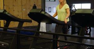 Vrouw die oefening op tredmolen in geschiktheidsstudio 4k doen stock videobeelden
