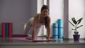 Vrouw die oefeningen voor benen op oefeningsmatten doet stock videobeelden