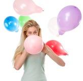 Vrouw die - omhoog ballons voor een partij blazen royalty-vrije stock fotografie