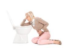 Vrouw die omhoog in het toilet werpt Royalty-vrije Stock Fotografie
