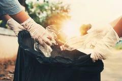 vrouw die omhoog huisvuil plastic fles voor het schoonmaken met de hand plukken royalty-vrije stock foto's