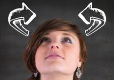 Vrouw die omhoog witte gebogen pijlen tegen grijze muur bekijken Royalty-vrije Stock Foto