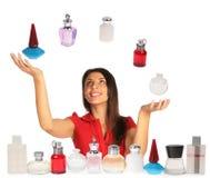 Vrouw die omhooggaande en het jongleren met parfums kijken stock afbeeldingen