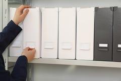 Vrouw die omslag met documenten van plank in archief nemen stock foto