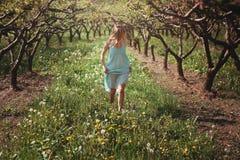Vrouw die onder bloemen lopen Stock Afbeelding