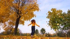 Vrouw die onder gele dalende bladeren dansen stock videobeelden