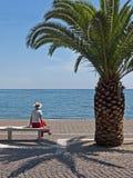 Vrouw die onder palm in zonneschijn wordt gezeten Royalty-vrije Stock Foto