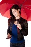 Vrouw die onderaan de Paraplu van de Telefoon kijkt Royalty-vrije Stock Afbeeldingen