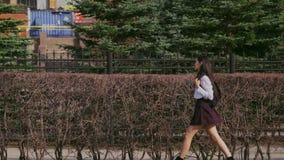 Vrouw die onderaan de straat na universiteit lopen Het Chinese meisje gaat met schooltas stock footage