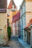 Vrouw die onderaan de straat van oude stad van Tallinn lopen Stock Foto's