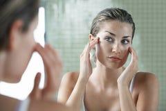 Vrouw die onderzoeken in Front Of Mirror stock afbeelding