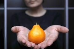 Vrouw die ongebruikelijke mandarijn in de hand houden royalty-vrije stock afbeelding