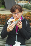 Vrouw die ongezonde kost buiten eet stock afbeeldingen