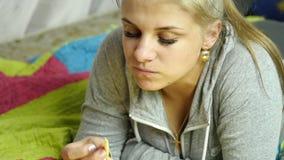 Vrouw die ongezonde kost met groot plezier eten het meisje eet frieten Langzame Motie stock footage