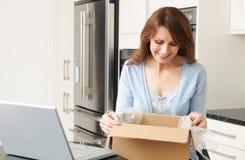 Vrouw die Online Aankoop thuis uitpakken royalty-vrije stock fotografie