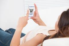 Vrouw die online op mobiele telefoon thuis winkelen Stock Foto's