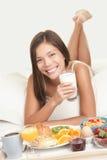 Vrouw die ontbijt in bed eet Stock Fotografie
