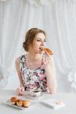 Vrouw die Ontbijt met eigengemaakte thee en verse croissants hebben Royalty-vrije Stock Foto's