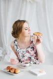 Vrouw die Ontbijt met eigengemaakte thee en verse croissants hebben Royalty-vrije Stock Foto