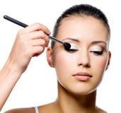 Vrouw die oogschaduw met borstel toepast Royalty-vrije Stock Afbeeldingen