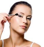Vrouw die oogschaduw met borstel toepast Royalty-vrije Stock Afbeelding